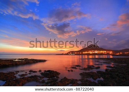 Amazing beautiful sunset reflection on the sea with rock, wave and mountain - stock photo
