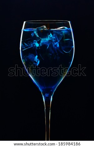 Amazing blue cocktail with ice cubes in high glass. Blue curacao liquor. - stock photo