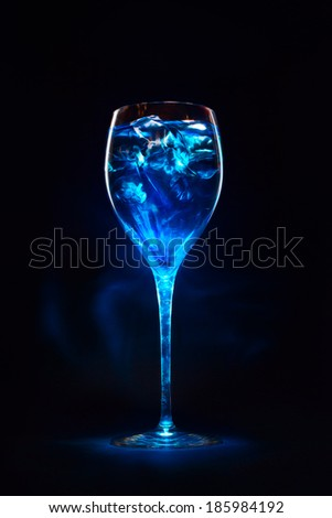 Amazing blue cocktail with ice cubes in high glass. Blue curacao liquor. Magic lights and shadows. - stock photo