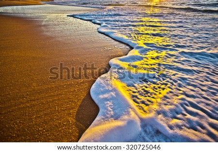 Amazing colours on the foaming waves rolling over the sand at sunset