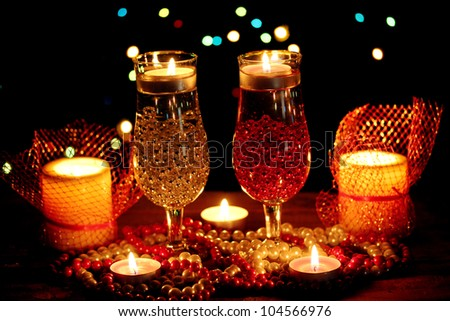 Amazing composition of candles and glasses on wooden table on bright background - stock photo