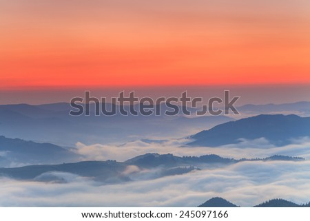 Amazing dawn sky over the misty mountains - stock photo