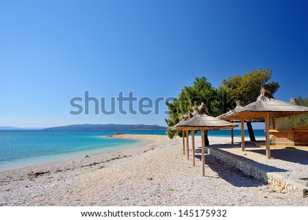 Amazing empty bay with crystal clear water and beach umbrellas in Croatia - stock photo