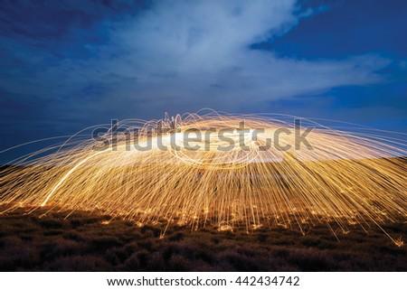 Amazing Fire dancing steel wool  in the twilight. - stock photo