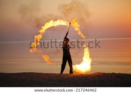 Amazing fire solo performance on the beach - stock photo
