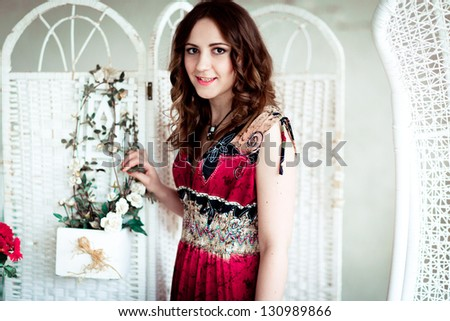 Amazing girl in a light dress standing near the screen with flowers