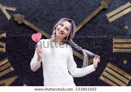 Amazing girl portrait in the white warm woolen sweater with gray silver hair with red and white lollipop and clock on the background. Happy time, positive emotions in Valentines day