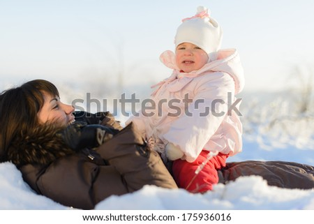 amazing girl sitting on her mother in snow - stock photo