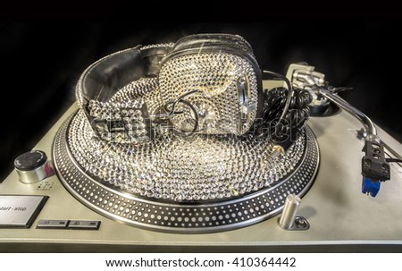 amazing handmade bling crystal covered headphones on a crystal record and turntable - stock photo