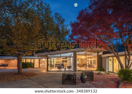 Amazing inside view of Modern Home with moonlight with beautiful tree in autumn, at night with seating arrangement and sliding full frame glass doors. Great Design Ideas. - stock photo