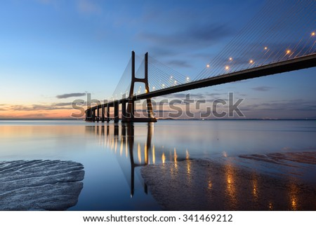 Amazing landscape of Lisbon with the bridge Vasco da Gama reflected Rio Tejo at sunrise. - stock photo