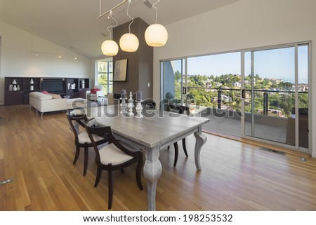 Amazing modern big dining area of hillside home with sliding glass doors leading to outdoors with balcony and breathtaking incredible view. - stock photo