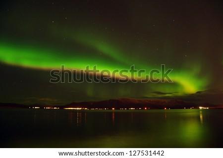 Amazing northern lights (Aurora borealis) on the Reykjavik coast, Iceland - stock photo