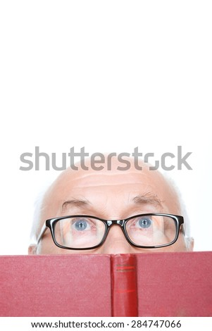 Amazing plot. Clever grandfather in glasses holding the book near his face and keeping glance up. - stock photo