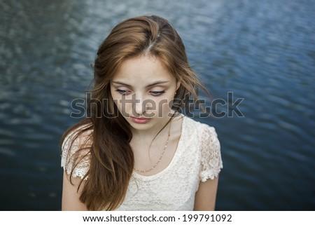 Amazing sad girl with big eyes on water background - stock photo