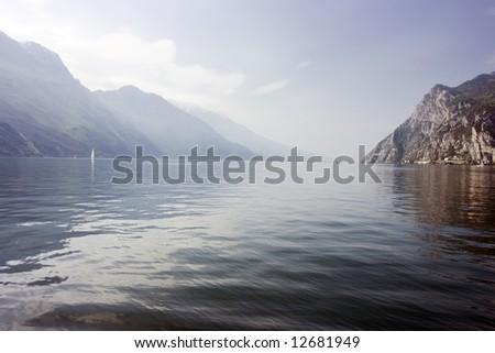 Amazing scenery of Garda Lake with mountains embracing water. - stock photo