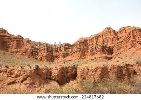 Amazing scenic orange rocks, screes of sandstone, walls carved away by erosion, canyon Uchterek, Kyrgyzstan. - stock photo