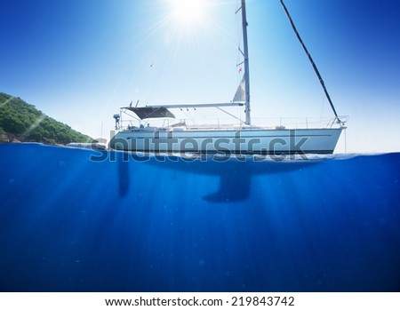 Amazing sunlight seaview to sailboat in tropical sea with deep blue underneath splitted by waterline - stock photo
