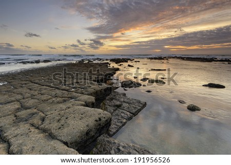 Amazing sunset on a Rocky beach on the west coast of Portugal - stock photo