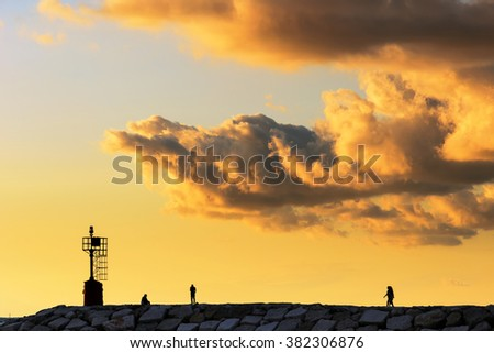 amazing sunset over the pier with people in summer - stock photo