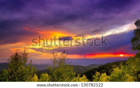 Amazing sunset over the Santa Fe Ski Basin featuring red, orange, purple, yellow, and other colors in the sky - stock photo