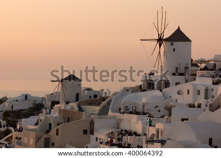 Amazing Sunset over white windmills in  town of Oia and panorama to Santorini island, Thira, Cyclades, Greece - stock photo