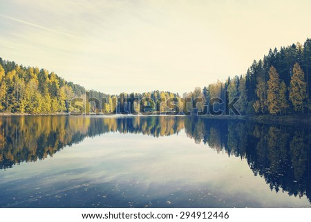 Amazing sunset scenery from Finland. Water and forest with reflections. Image has a vintage effect applied.