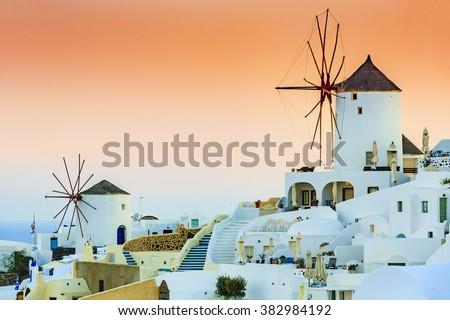 Amazing sunset view of windmills in Oia village on Santorini island in Greece. - stock photo
