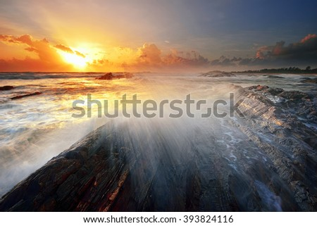 Amazing sunset with motion waves splashing on the rock at the beach. Nature composition. - stock photo