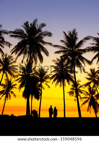 amazing sunset with silhouette of couple and coconut tree - stock photo