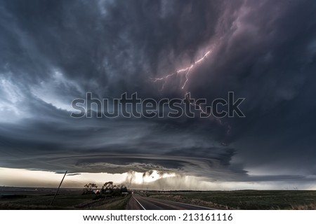 Amazing supercell lighted up by lightnings at dusk - stock photo