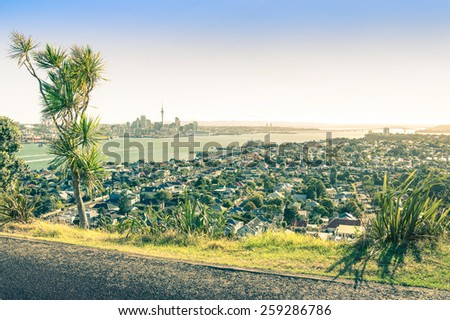 Amazing view of Auckland skyline and territory from Mount Victoria in Devonport area - High angle sight of the New Zealand capital - Vintage filtered look with low sun out of the right side of image - stock photo