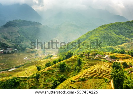 Amazing view of rays of sunlight illuminating green rice terraces through storm clouds at highlands of Sapa District, Lao Cai Province, Vietnam. Sa Pa is a popular tourist destination of Asia.