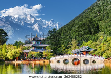 Amazing view of the Jade Dragon Snow Mountain and the Black Dragon Pool, Lijiang, Yunnan province, China. The Suocui Bridge over pond and the Moon Embracing Pavilion in the Jade Spring Park. - stock photo