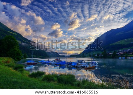 Amazing view of the Lungerersee lake with yachts in the morning mist. Lungern village, Switzerland, Europe. - stock photo