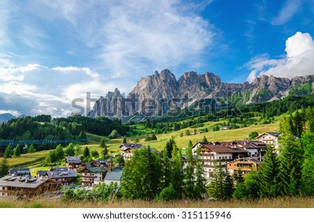 Amazing view on Cristallo Mountains with alpine village on sunny summer day, The Dolomites Mountains, Italy - stock photo