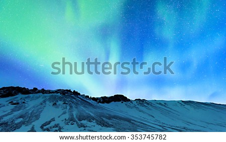 Amazing view on the Northern light and high mountains landscape covered with snow, forces of nature, Aurora Borealis, Iceland - stock photo