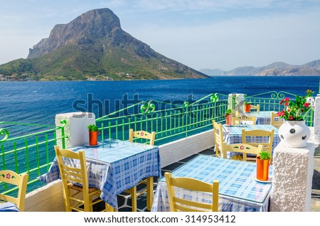 Amazing view on typical Greek restaurant with terrace having clear view on sea landspace with islands, Greece - stock photo