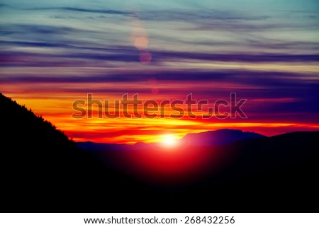Amazing view with colorful sunset and sun rays over mountain landscape - stock photo