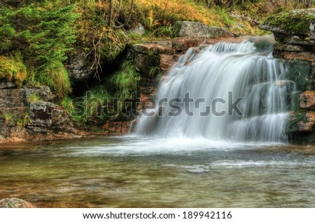 Amazing waterfall in a wooded mountainous landscape  - stock photo