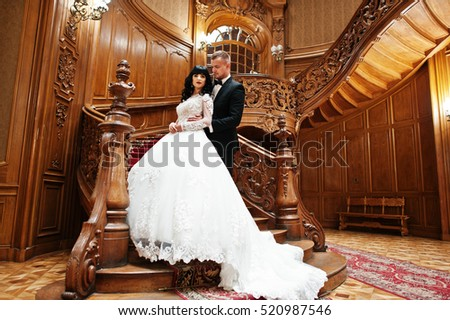 Amazing wedding couple on big wooden stairs at rich palace.