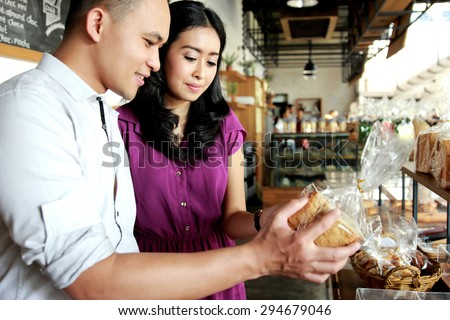 amazing young couple comparing bread at bakery shop - stock photo