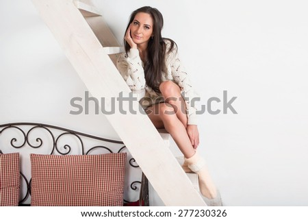 Amazingly beautiful brunette charming woman in white sweater is sitting at the stairs at home - stock photo