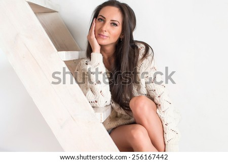 Amazingly beautiful brunette sexy charming woman in white sweater is sitting at the stairs at home - stock photo
