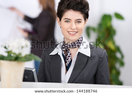 Amazingly beautiful female well dressed receptionist welcoming the guests with a charming smile. - stock photo