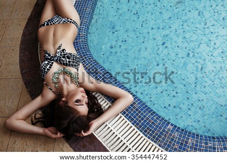 Amazingly beautiful girl with slim figure is relaxing in the swimming pool - stock photo