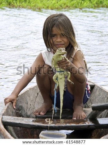 AMAZON RIVER - CIRCA SEPTEMBER 2010. Unidentified young girl holds a baby caiman at the Amazon River, Brazil, CIRCA September 2010. - stock photo