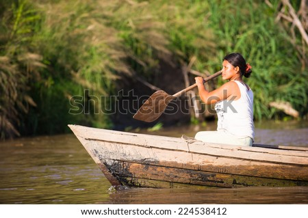 AMAZONIA, PERU - NOV 10, 2010: Unidentified Amazonian woman rows a wooden boat. Indigenous people of Amazonia are protected by COICA (Coordinator of Indigenous Organizations of the Amazon River Basin) - stock photo