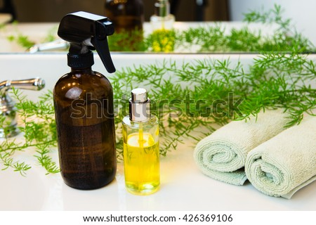 Amber and clear glass spray bottles. Rolled green towels in a spa setting. Green plant decor in background. Bathroom white countertop. - stock photo
