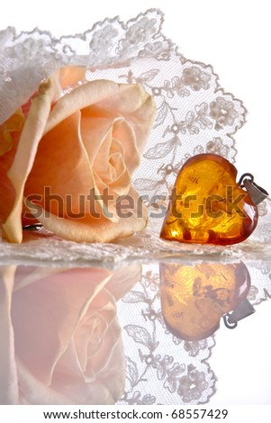 Amber heart and roses lying on a lace veil;